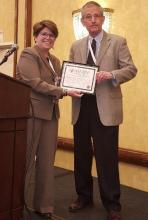 Photo: Elyse Summers, JD, AAHRPP President and CEO presenting the Friends of AAHRPP award to Andy Bertolatus, MD, University of Iowa primary IRB Chair